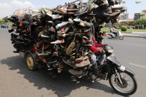 Cambodian salesman straps hundreds of shoes to motorcycle in bid to sell them