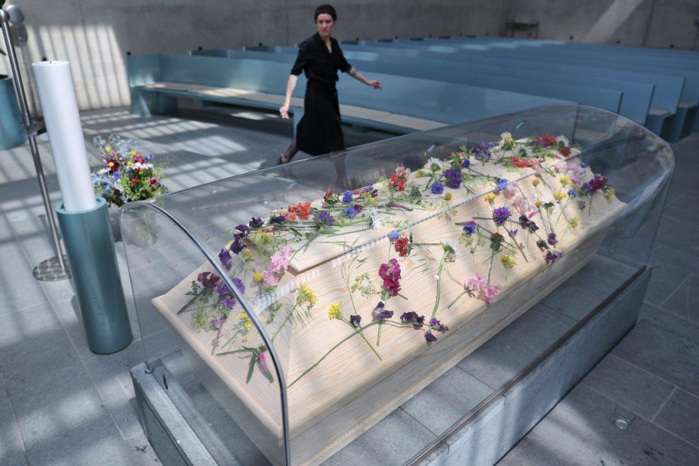Coronavirus victim's coffin placed under plastic shield to prevent corpse spreading Covid to mourners